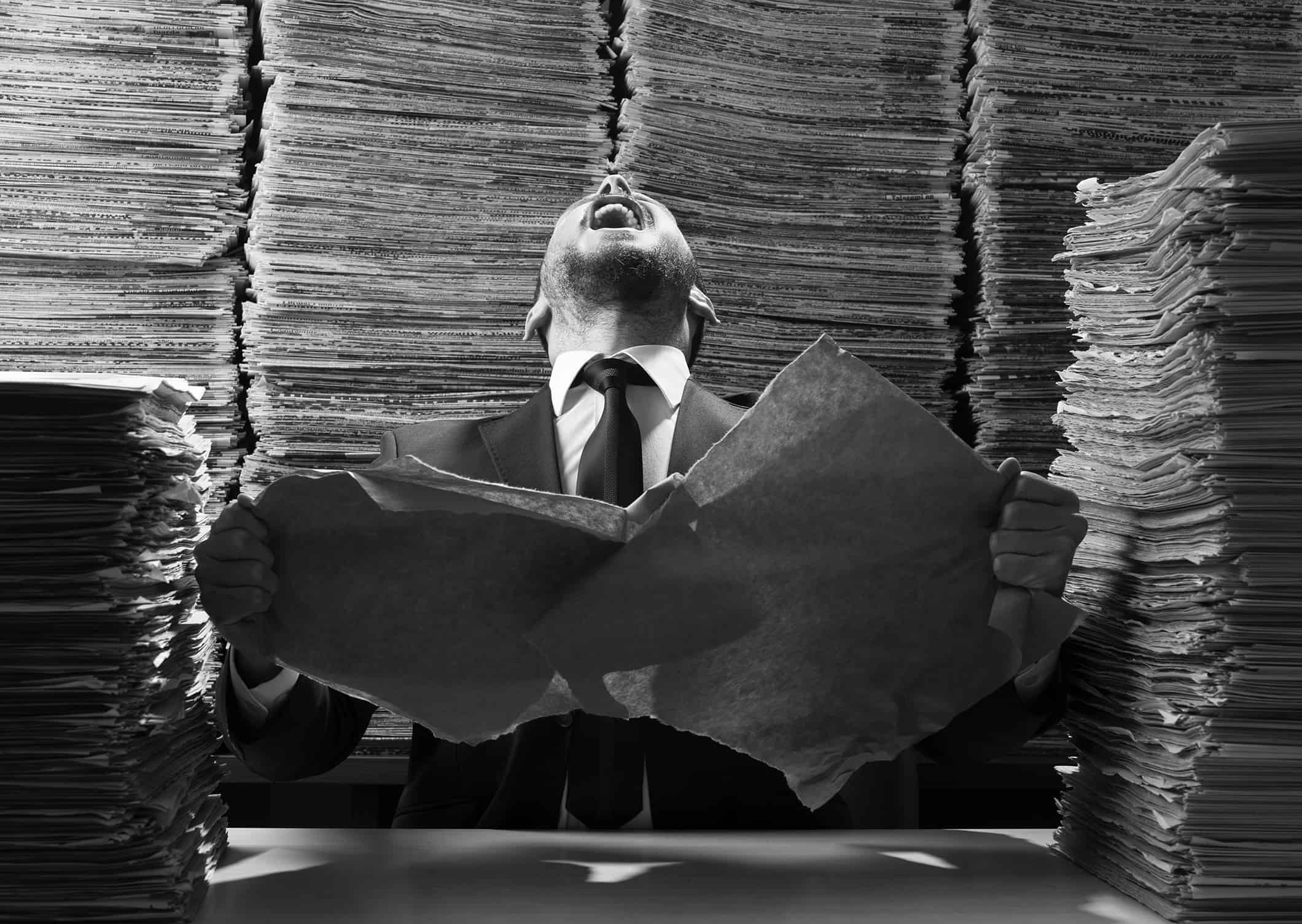 Office worker tearing up papers and screaming out due to red tape